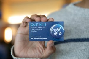 Empowering Carolina attendee holds out Count Me In card and button in front of him