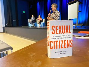 """The front cover of the book, """"Sexual Citiens: A Landmark Study of Sex, Power, and Sexual Assault on Campus"""" propped up on a table with Vice Chancellor Becci Menghini speaking int he background."""